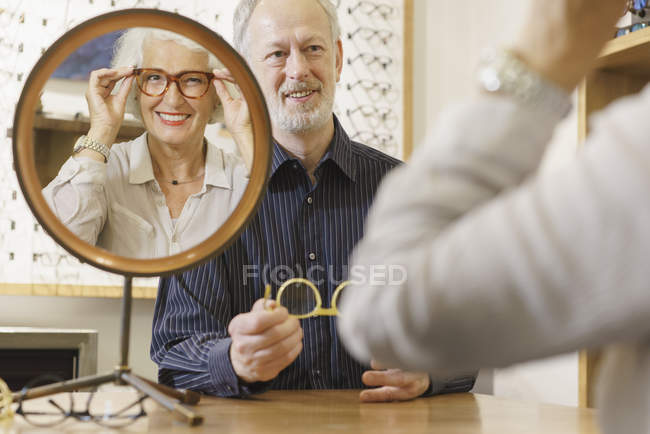 Optician assisting smiling woman choosing eyeglasses in store — Stock Photo