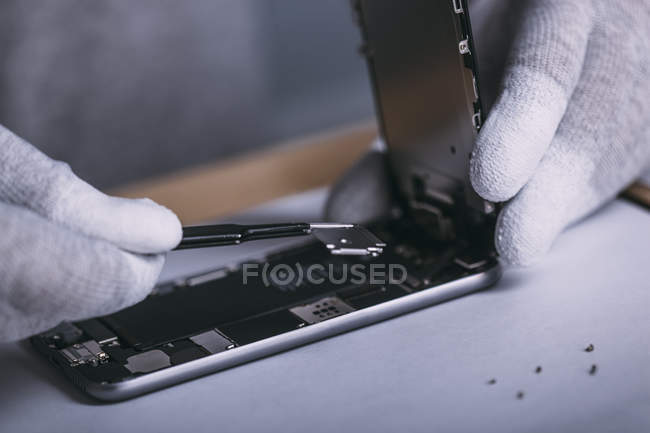 Detail image of male technician repairing smart phone at electronics store — Stock Photo