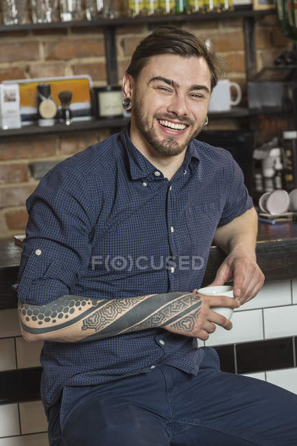 Portrait of cheerful hairdresser sitting with coffee at bar counter in barber shop — Stock Photo