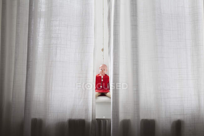 Boneca sentada no peitoril da janela atrás de cortinas — Fotografia de Stock