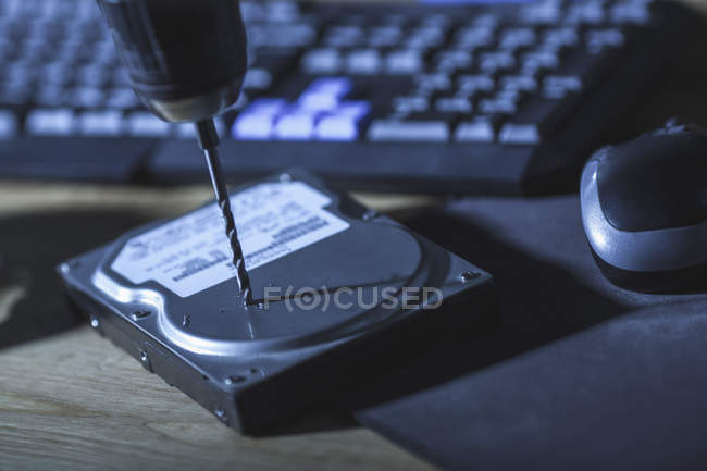 Close-up of drill on hard drive by computer keyboard at table — Stock Photo