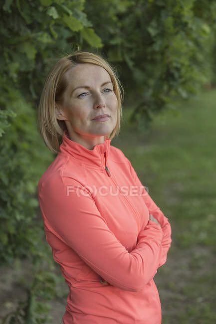 Thoughtful mature woman standing with arms crossed in park — Stock Photo