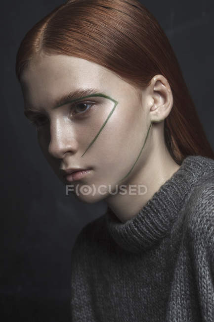 Крупный план девочки-подростка, смотрящей в сторону с краской на черном фоне — стоковое фото