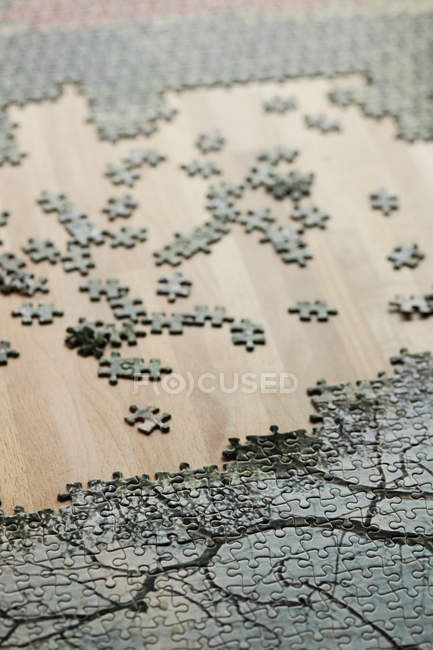 Close up view of jigsaw puzzle with mixed pieces on wooden table — Stock Photo