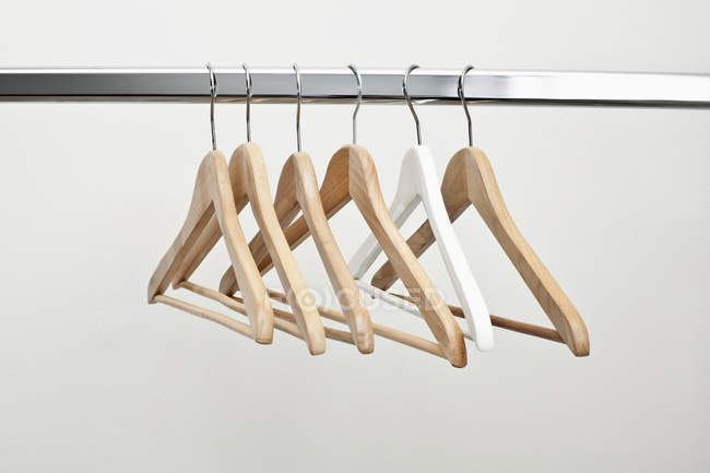 Row of empty coat hangers on metal rack against white wall — Stock Photo