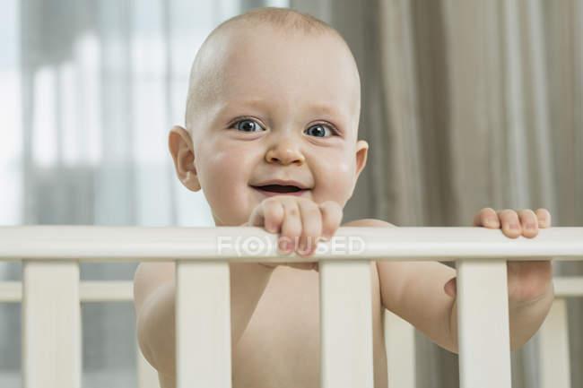 Bambino in piedi in culla al chiuso — Foto stock