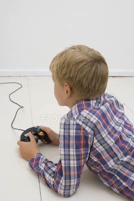 Молодий хлопчик лежить на підлозі і утримуючи control відеоігор — стокове фото