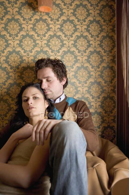 Молодая пара, сидящая вместе на бобовом мешке — стоковое фото