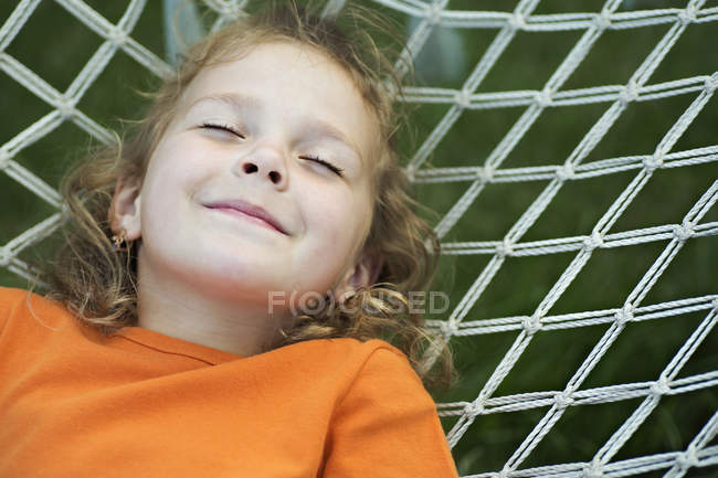 A young smiling girl lying on a hammock with her eyes closed — Stock Photo