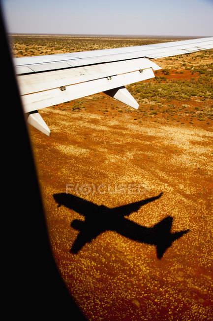Vista do plano de paisagem árida com silhueta de avião — Fotografia de Stock