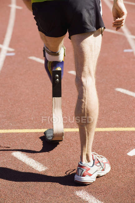 Low section of athlete with prosthetic leg standing at starting line of racing track — Stock Photo