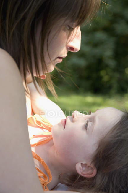 Mother and daughter lying down on backyard together — Stock Photo
