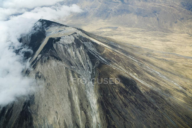 Aerial view of clouds flowing over volcano — Stock Photo