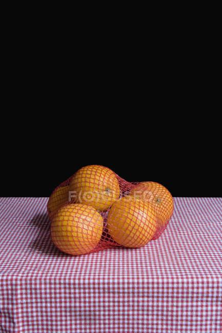 Gruppe von Orangen im Netz auf karierten Tischdecke — Stockfoto