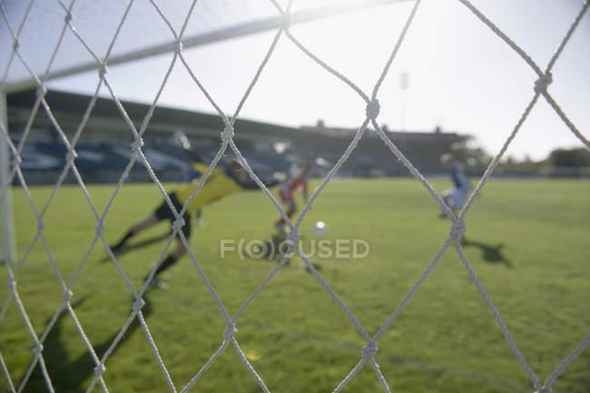 Un partido de fútbol en el campo durante el día - foto de stock