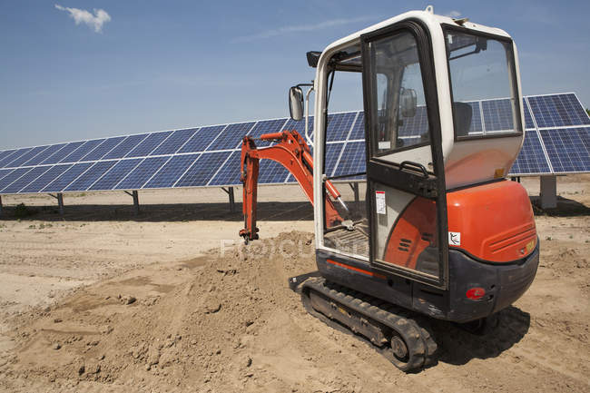 Mechanical digger on sand by solar panel construction site — Stock Photo