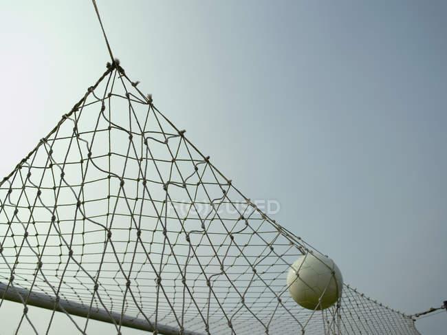 Crop soccer ball in goal net — Stock Photo