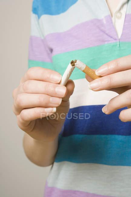 Midsection della sigaretta di rottura della donna nella metà — Foto stock