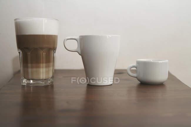 Tres tipos diferentes de tazas de café en fila - foto de stock