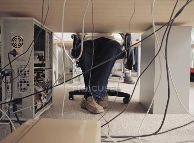 Seção de baixo do homem sentado à mesa e cabos conectados à parte traseira do computador — Fotografia de Stock