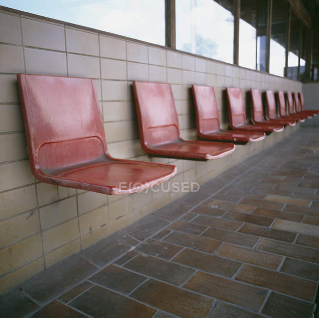 Red plastic seats in row on tiled wall — Stock Photo