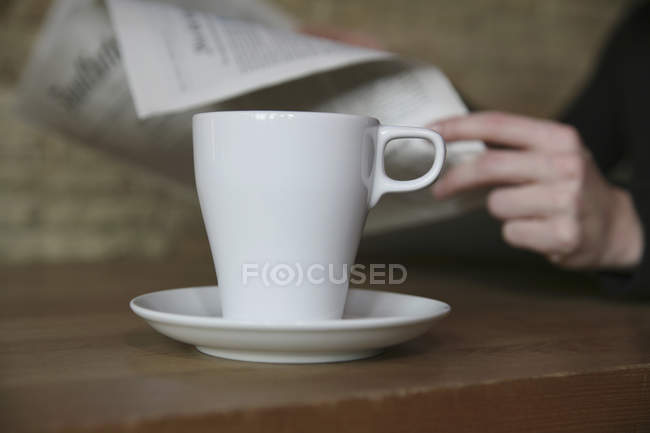 Coffee cup on table in cafe with woman sitting in background reading newspaper — Stock Photo