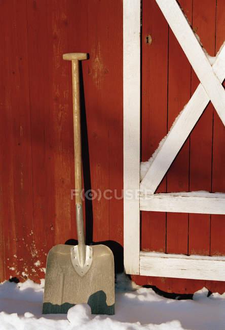 Pala da neve contro fienile di legno rosso — Foto stock