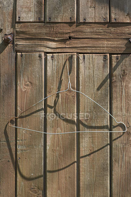 Wire coat hanger on rural wooden wall — Stock Photo