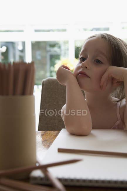 Маленькая девочка сидит за столом с блокнотом для рисования и цветными карандашами — стоковое фото