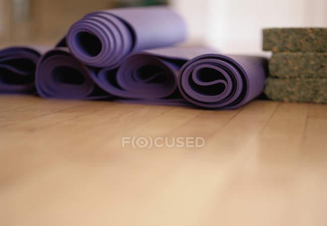Вид поверхности свернутых ковриков для упражнений на полу — стоковое фото