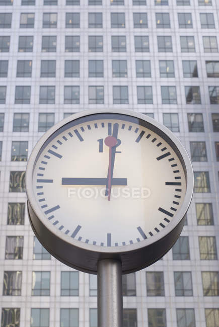 Clock face showing in front of office building — Stock Photo