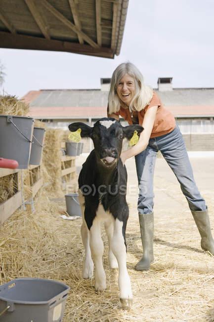 Портрет усміхається жінка, стоячи з теля в двору — стокове фото