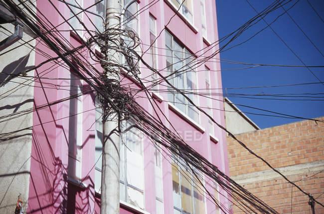 Kreuzung von Stromleitungen vor rosa Gebäude — Stockfoto