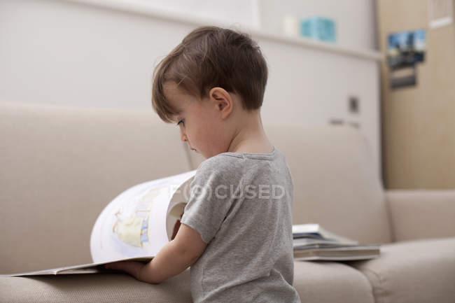 Kleiner Junge betrachtet man ein Bilderbuch auf sofa — Stockfoto