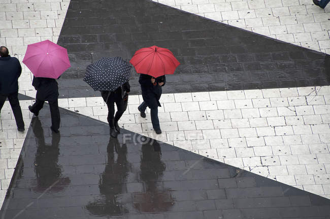 Pedestrians walking with umbrellas — Stock Photo