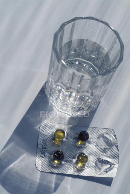 Cápsulas en paquete junto al vaso de agua en la mesa - foto de stock