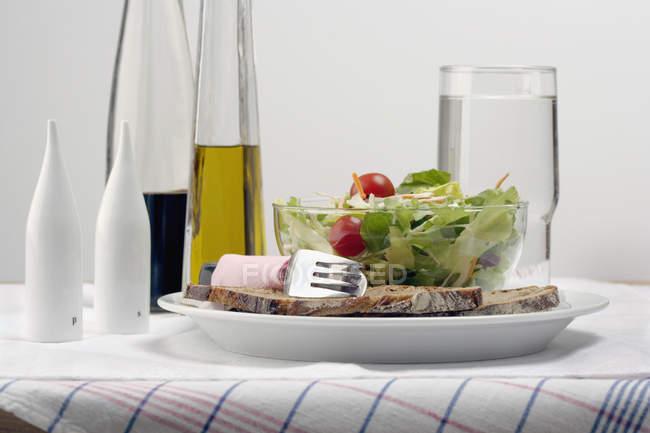 Salat und Brot auf dem Tisch neben Olivenöl und Balsamicoessig — Stockfoto