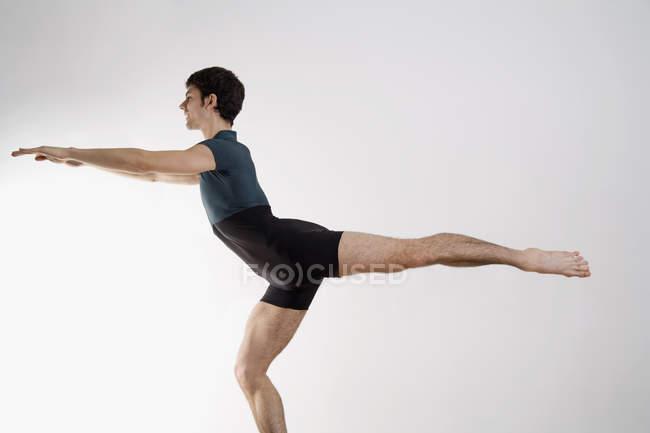 Homem praticando Pilates em fundo branco — Fotografia de Stock