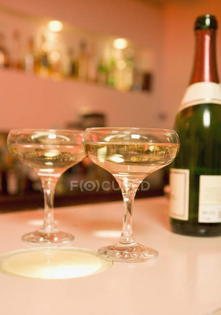 Два бокала шампанского рядом бутылка на барной стойкой — стоковое фото