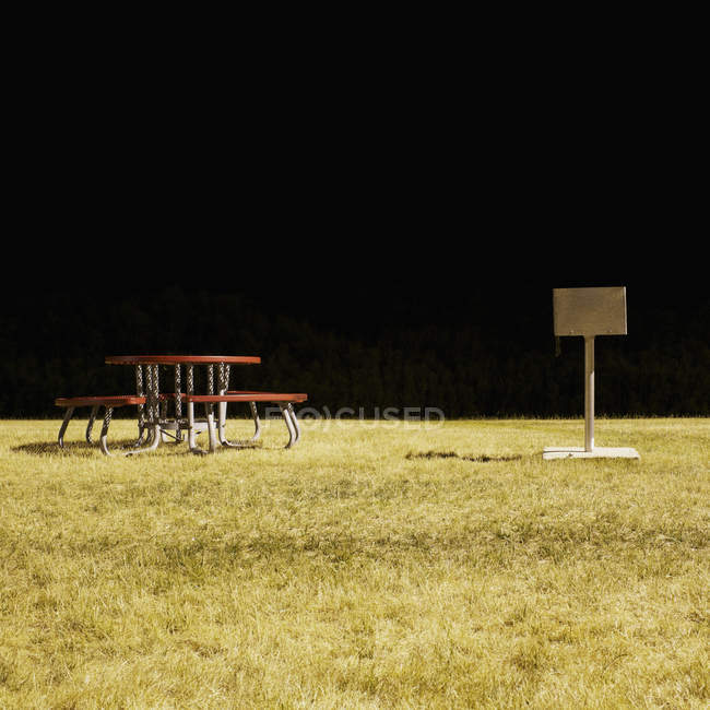 Uma mesa de piquenique e churrasco num parque à noite, longa exposição — Fotografia de Stock