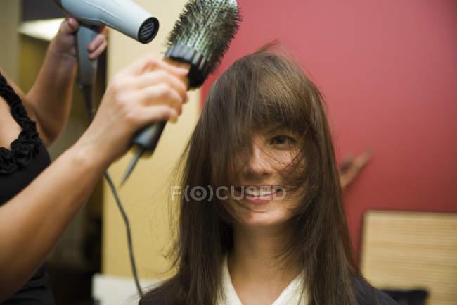 Un brushing de styliste un cheveux de la jeune femme — Photo de stock