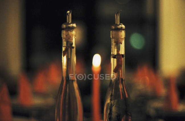Crop bottles of olive oil in restaurant at night — Stock Photo
