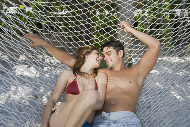 Happy young couple lying down on hammock — Stock Photo