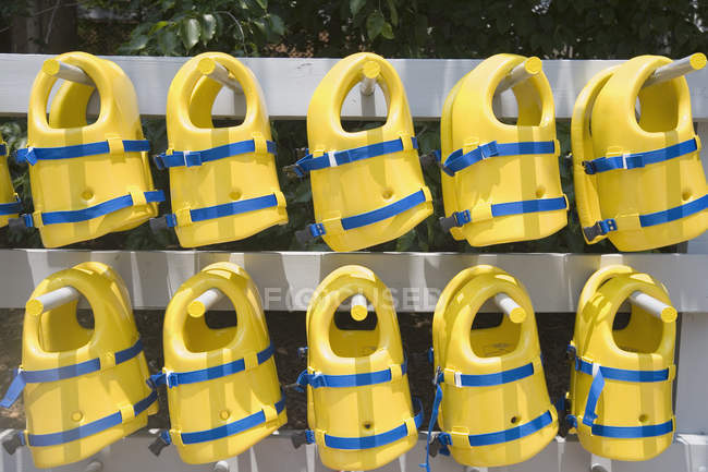 Rows of life jackets arranged on rack — Stock Photo