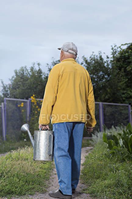Senior man carrying metal watering can on backyard — Stock Photo