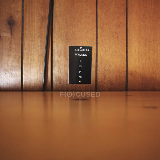Sign posted on wood paneling detailing TV channels in motel — Stock Photo