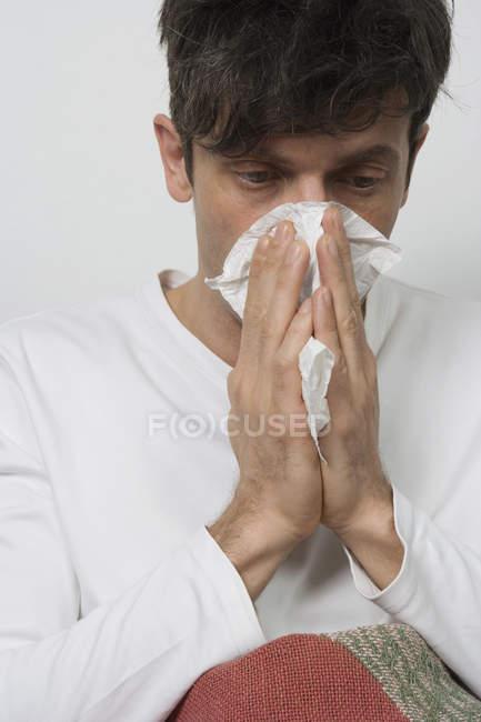 Primo piano di uomo che soffia il naso su priorità bassa bianca — Foto stock