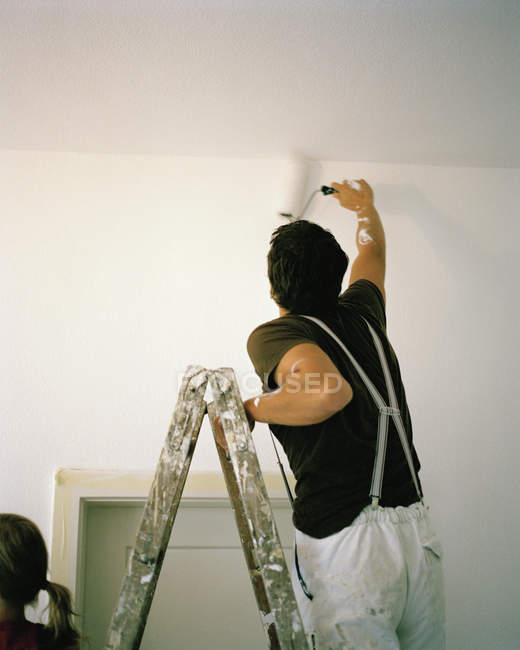 Rear view of man standing on ladder and painting wall with paint roller — Stock Photo