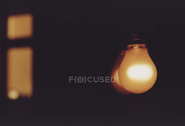 Light bulb reflecting in glass — Stock Photo