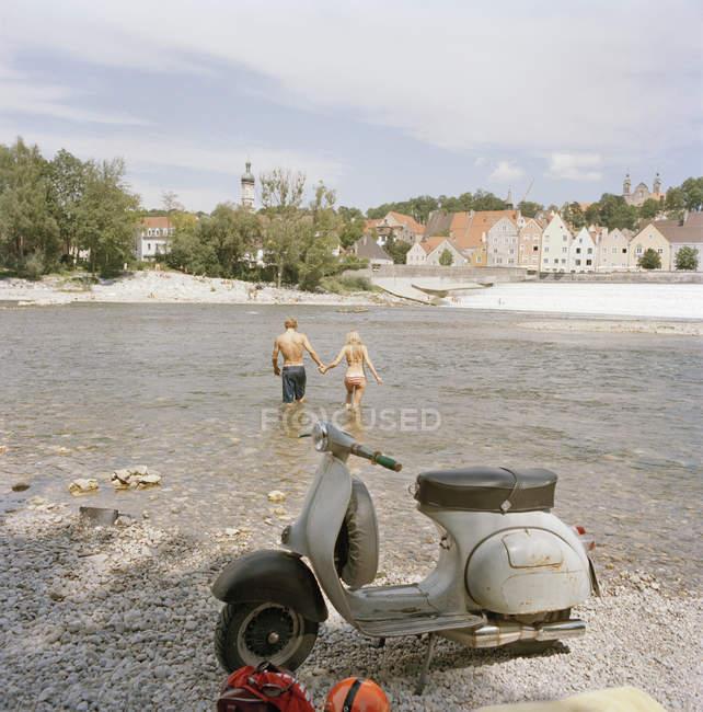 Motorroller parkt am Ufer, während junges Paar ins Wasser geht — Stockfoto